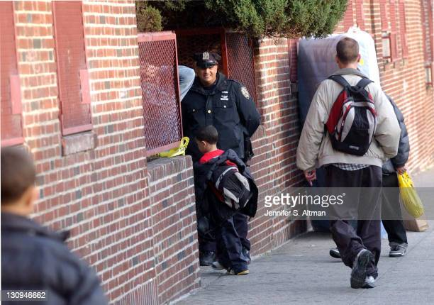 A police officer stands guard as children enter 1031 Freeman Street in the Bronx NY where Kathy Nguyen lived Nguyen died of anthrax inhalation