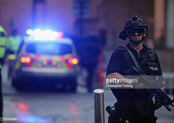 A police officer stands guard as Dale Cregan arrives in an armed convoy to face charges of murder and attempted murder at Manchester City...
