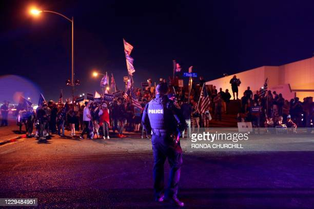 Police officer stands guard as Donald Trump supporters protest the Nevada vote outside Clark County Election Department on November 5 in North Las...