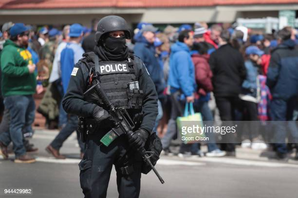A police officer stands guard as fans arrive at Wrigley Field for the Chicago Cubs home opener on April 10 2018 in Chicago Illinois The game against...