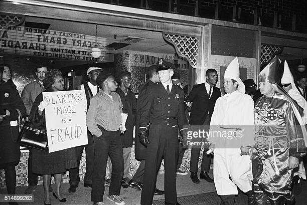 A police officer stands guard as Ku Klux Klansmen protesting a desegregated hotel pass a group of African Americans protesting a segregated...