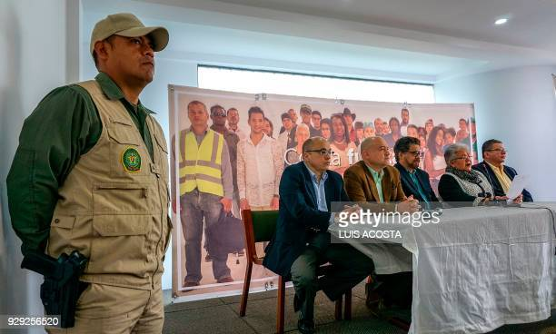 A police officer stands guard as leaders of the Common Alternative Revolutionary Force political party offer a press conference in Bogota on March 8...
