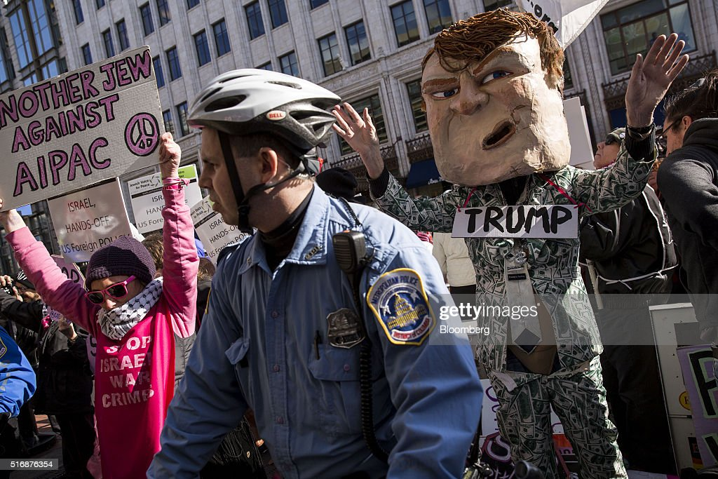 A police officer stands guard as protesters demonstrate outside the American Israeli Public Affairs Committee (AIPAC) policy conference in Washington, D.C., U.S., on Monday, March 21, 2016. The presidential race will take a detour from domestic sniping today as Hillary Clinton, Donald Trump and Trump's two Republican opponents converge on Washington to address a key pro-Israel group. Photographer: Drew Angerer/Bloomberg via Getty Images