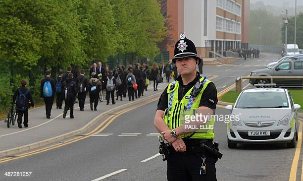 A police officer stands guard as pupils arrive for school at Corpus Christi Catholic College in Leeds northern England on April 29 following the...