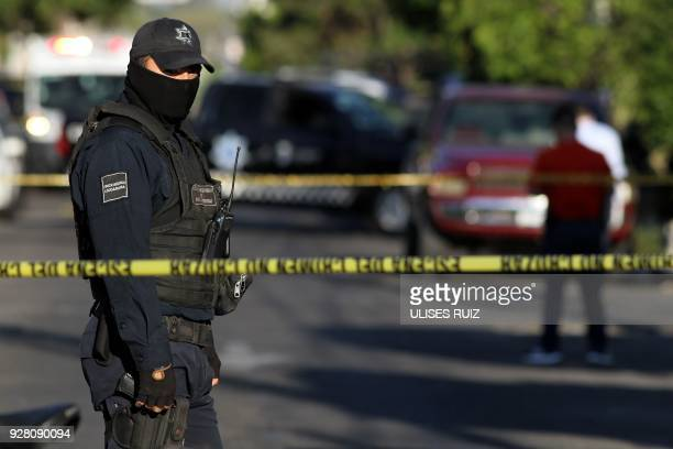 A police officer stands guard as state prosecutors inspect a pickup truck found abandoned with the bodies of six men some of them decapitated which...