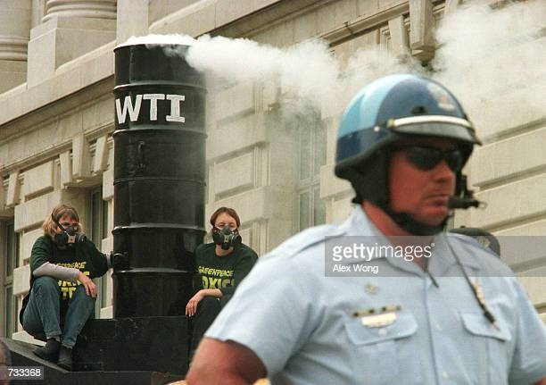 A police officer stands guard as two Greenpeace demonstrators left chain themselves to a mock incinerator smokestack atop a bus during a protest...