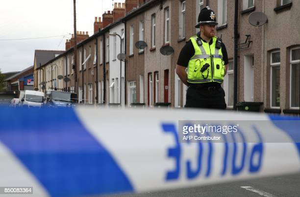 A police officer stands guard at a police cordon near to a house in Newport south Wales on September 20 as they continue their investigations into...