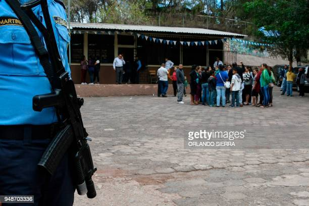 A police officer stands guard at a school in Tegucigalpa on April 18 2018 Students are also victims of the prevailing insecurity in Honduras where...