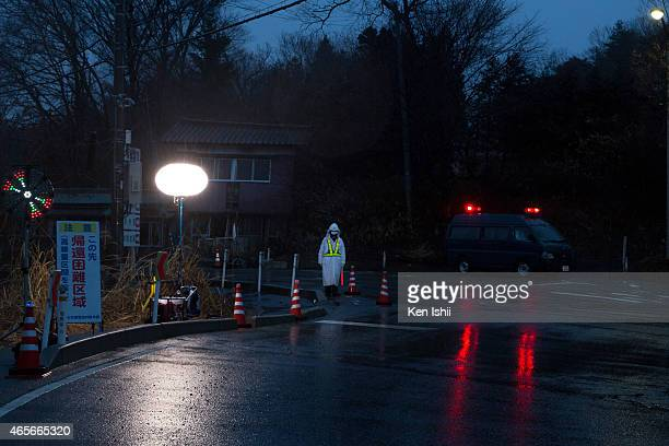 Police officer stands guard at checkpoint to the town within 10km the Fukushima Daiichi Nuclear Power Plant on March 9 2015 in Tomioka town Fukushima...
