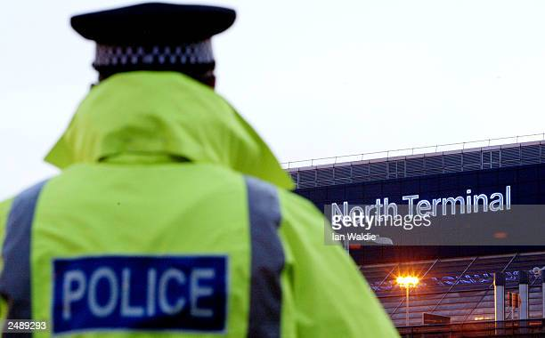 Police officer stands guard at Gatwick airport's north terminal after a security scare February 13, 2003 in Gatwick, United Kingdom. Part of Gatwick...