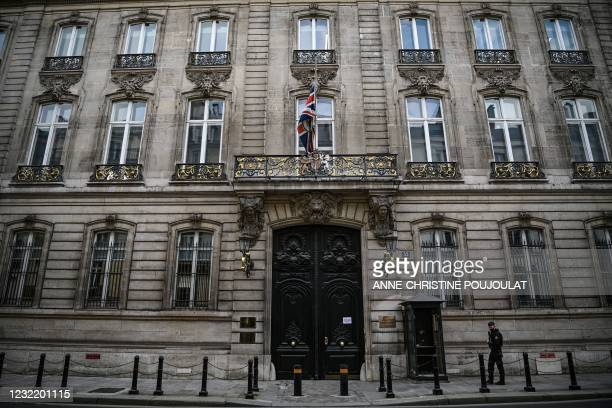 Police officer stands guard at the entrance of the British Embassy where the Britain's national flag, the Union Jack, flies at half-mast, in Paris on...