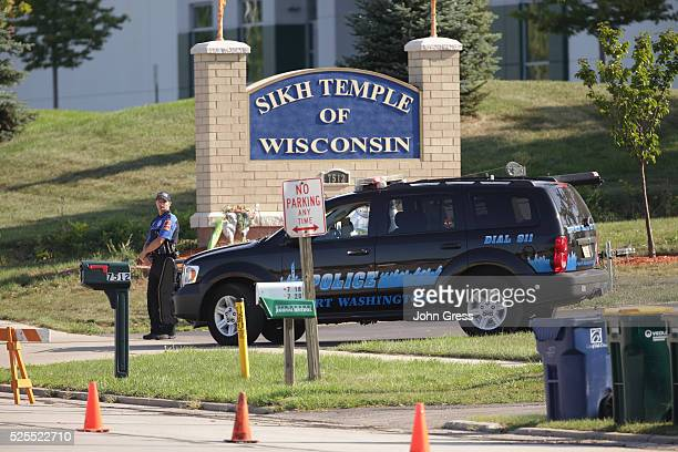 A police officer stands guard at the entrence to the Sikh Temple in Oak Creek Wisconsin on August 7 2012 A gunman killed six people and critically...