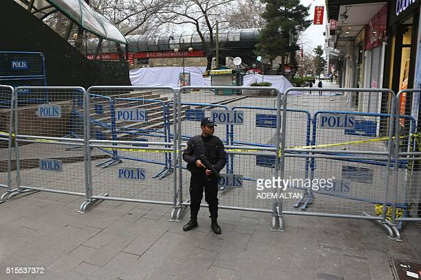 A police officer stands guard at the security perimeter around the scene of an explosion on March 14 2016 the day after a suicide car bomb ripped...