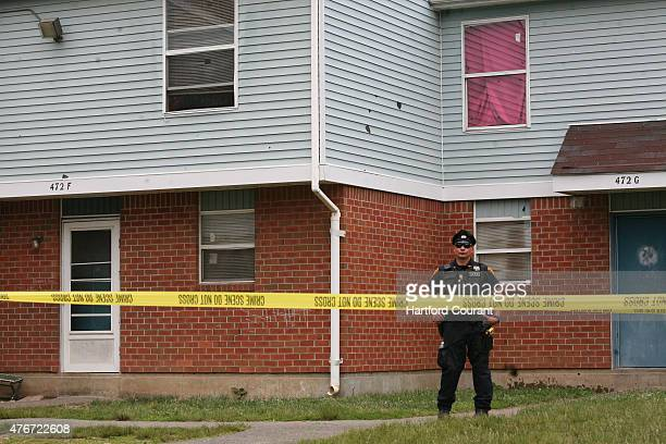 A police officer stands guard at the Trumbull Gardens housing complex in Bridgeport Conn on Thursday June 12 as police investigate the scene where...