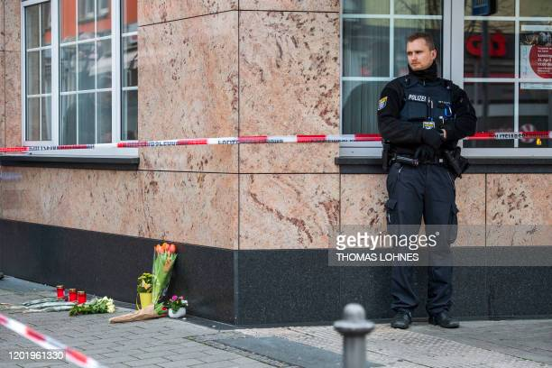 A police officer stands guard beside candles and flowers near one of the shooting targets on February 20 at the Heumarkt in the centre of Hanau near...