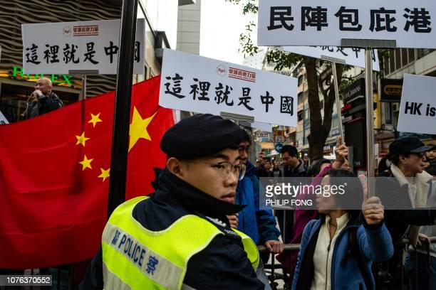 A police officer stands guard in front of a group of proBeijing supporters as they chant slogans and display placards reading 'This is China' during...