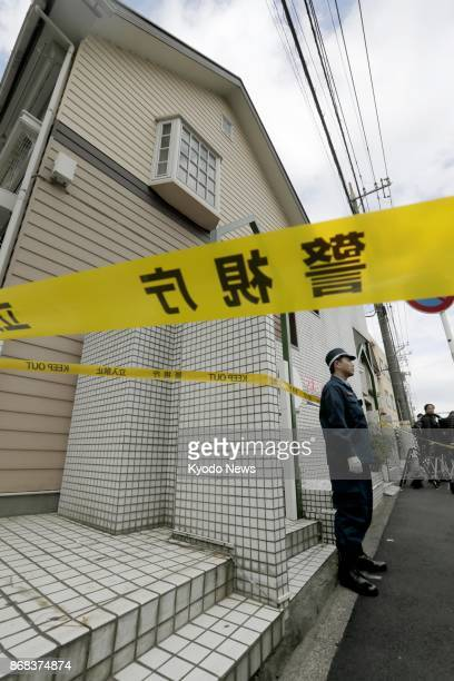 A police officer stands guard in front of an apartment house in Zama Kanagawa Prefecture where police found nine bodies in one of its units The...