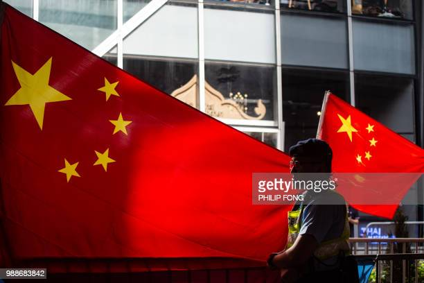 A police officer stands guard in front of Chinese flags as proBeijing demonstrators hold a counterrally during a protest march in Hong Kong on July 1...