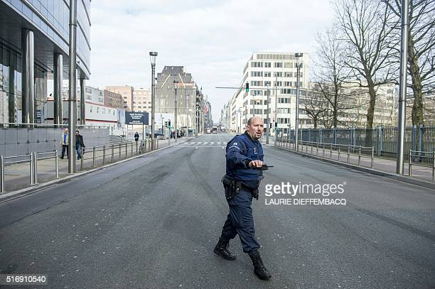 TOPSHOT A police officer stands guard in the Rue de la Loi following its evacuation after an explosion at theMaalbeek subway station in Brussels on...