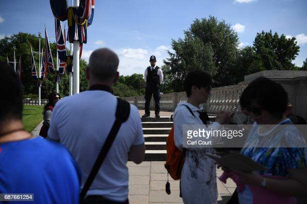 A police officer stands guard near Buckingham Palace as tourists pass on May 24 2017 in London England UK terror status is elevated to Critical in...
