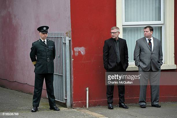 A police officer stands guard near mourners as the funeral of murdered prison officer Adrian Ismay takes place on March 22 2016 in Belfast Northern...