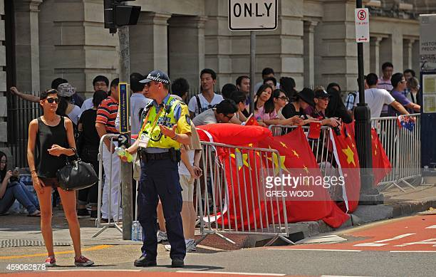 A police officer stands guard next to members of the local Chinese community as they wait to catch a glimpse of China's President Xi Jinping as he...