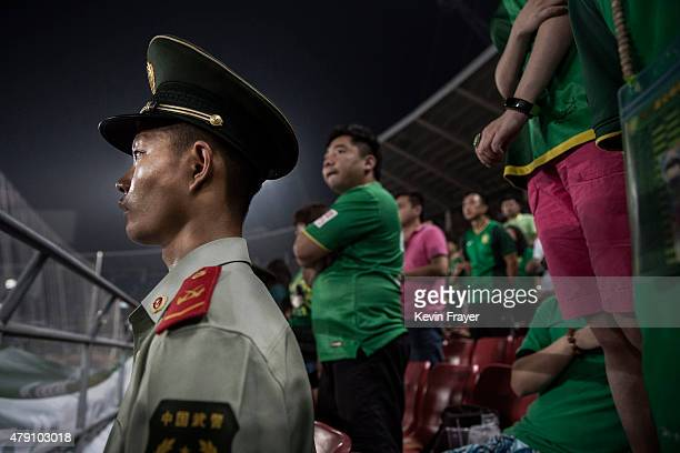 A police officer stands guard next to supporters and fans of the Beijing Guoan FC celebrate during the team's match against Chongcing Lifan FC during...