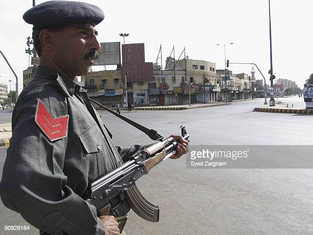 Police officer stands guard on a deserted street during a strike called by Islamic opposition parties of the Muttahida Majilis-e-Amal alliance June...