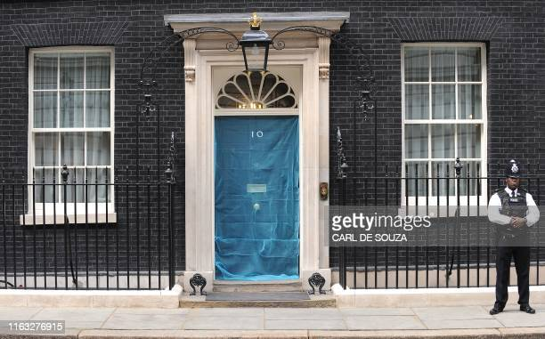 A police officer stands guard outside 10 Downing Street in London on April 20 2009 A mosquito net was placed over the door of number 10 as part of a...