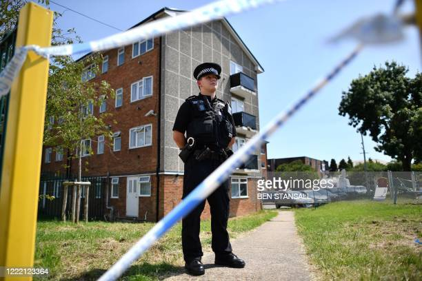 Police officer stands guard outside a cordoned off block of flats where the suspect of a multiple stabbing incident lived in Reading, west of London,...