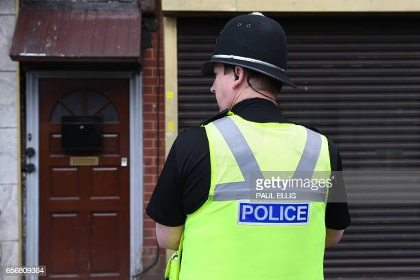 Police officer stands guard outside a residential building in Birmingham which was raided by anti-terror forces in the early hours on March 23, 2017....