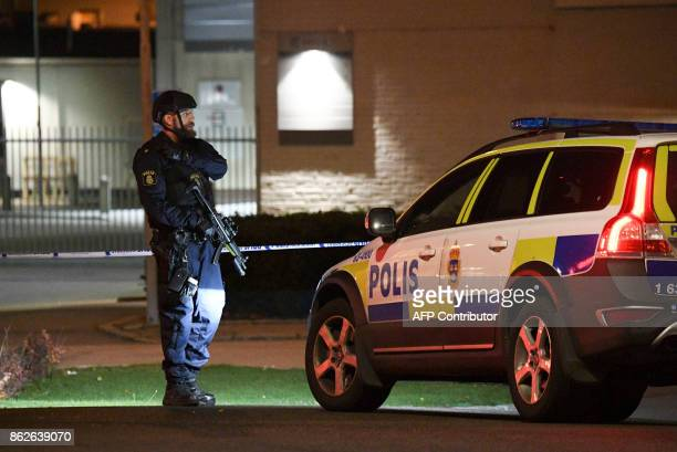 A police officer stands guard outside a security perimeter set around the area surrounding the police station in Helsingborg on October 18 after a...