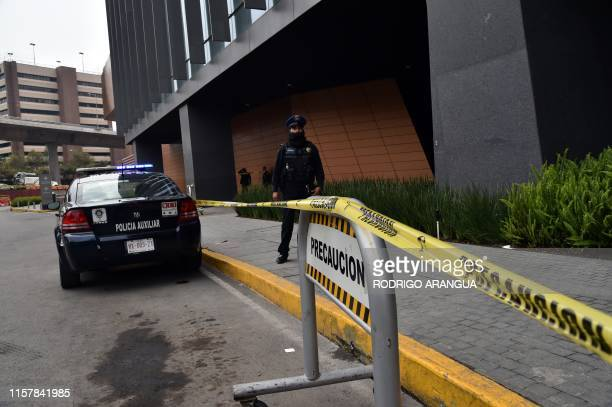 Police officer stands guard outside a shopping mall in Mexico City on July 26 two days after two Israelis with mafia links were shot dead in a...