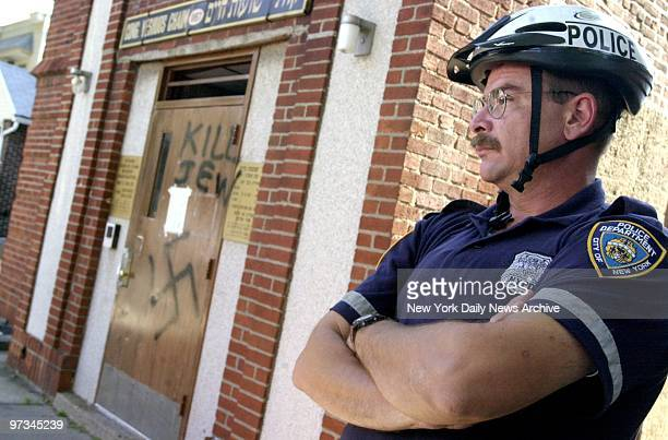 Police officer stands guard outside a synagogue Congregation Yeshuous Chaim on E 13th St in Midwood Brooklyn where the door is defaced with...