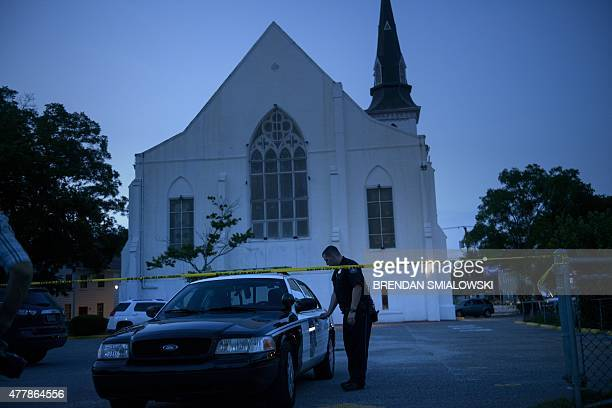 Police officer stands guard outside Emanuel AME Church June 20, 2015 in Charleston, South Carolina. Thousands of mourners clutching red and white...