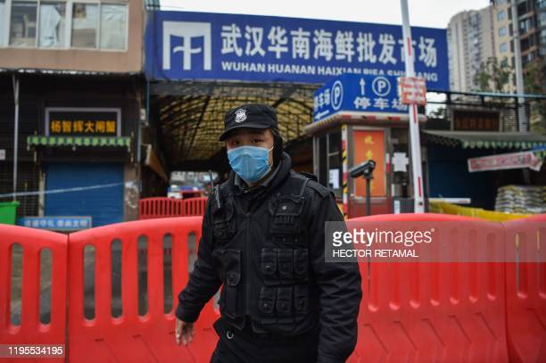 A police officer stands guard outside of Huanan Seafood Wholesale market where the coronavirus was detected in Wuhan on January 24 2020 The death...