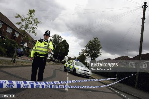 Police officer stands guard outside of Walton Drive after it was closed off following a police raid on a house on August 10, 2006 in High Wycombe,...