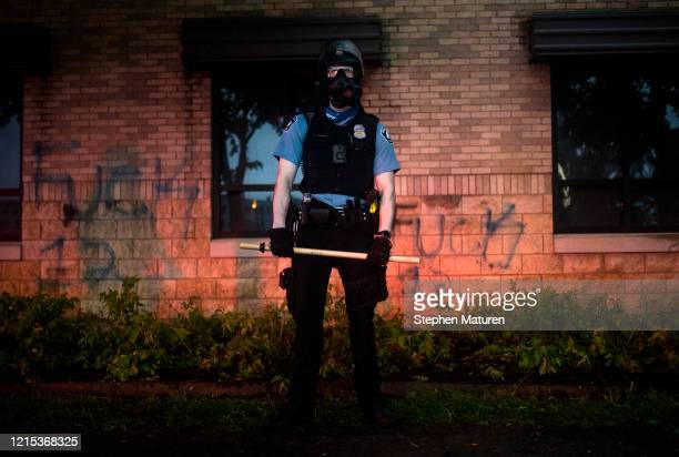 A police officer stands guard outside the 3rd Precinct Police Precinct during clashes with protesters on May 26 2020 in Minneapolis Minnesota Four...