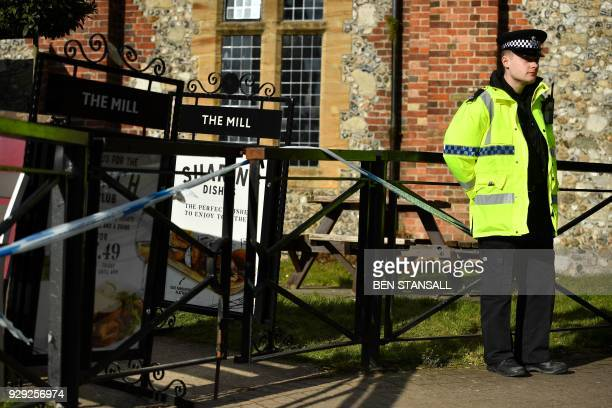 A police officer stands guard outside The Mill pub close to The Maltings shopping centre in Salisbury southern England on March 8 2018 which was...