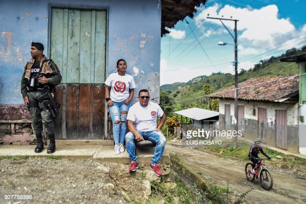 TOPSHOT A police officer stands guards next to members of the Common Alternative Revolutionary Force political party during a campaign rally for the...