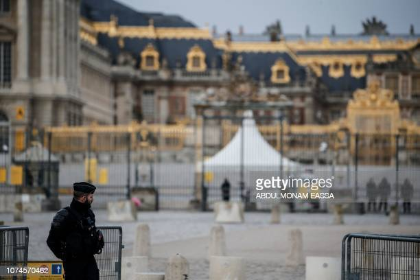 A police officer stands in a front of the Chateau de Versailles in Versailles outside Paris during a 'Yellow Vests' demonstration on December 22 2018...