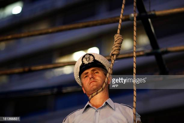 A police officer stands in a mock gallows outside the Finance Ministry during a protest against budget cuts in Athens on September 6 2012 Nearly 2000...