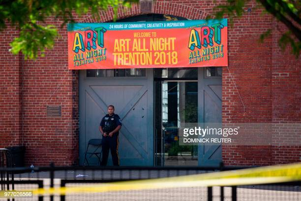 A Police officer stands in front as other officers inspect the crime scene at the Roebling Market on June 17 the morning after a shooting at an...