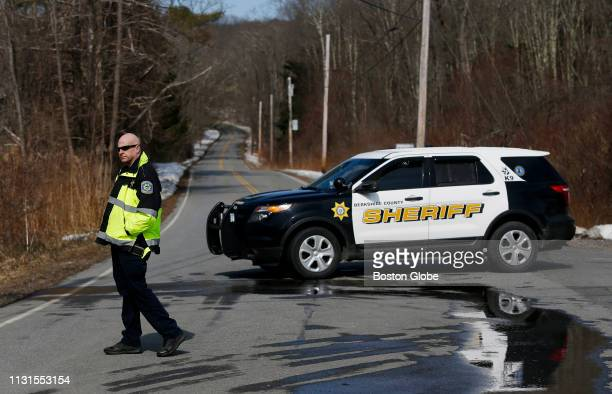 A police officer stands in front of a blocked off section of Home Road in Sheffield MA where five people were found dead following a house fire on...