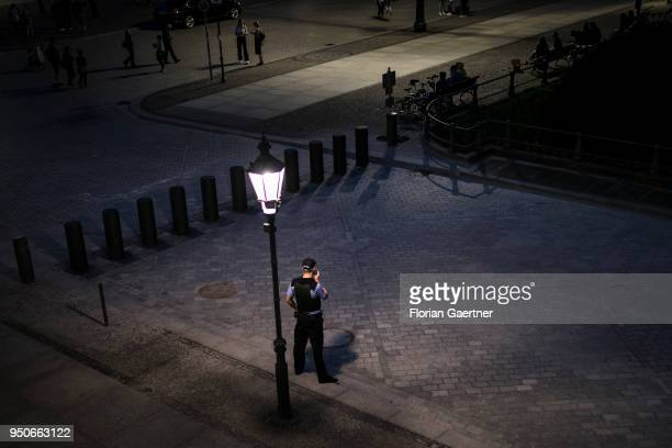 A police officer stands in front of a lantern at the place 'Pariser Platz' on April 19 2018 in Berlin Germany