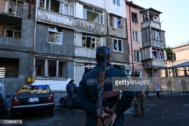 Police officer stands in front of an apartment building that was supposedly damaged by recent shelling in the breakaway Nagorno-Karabakh region's...