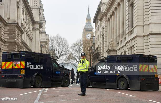 A police officer stands in front of armoured police personnel carriers on a street leading to the Houses of Parliament in central London on March 24...