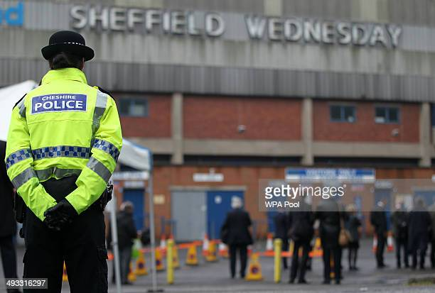 Police officer stands in front of members of the press outside the Hillsborough stadium in Sheffield as jurors on the inquest into the deaths of 96...