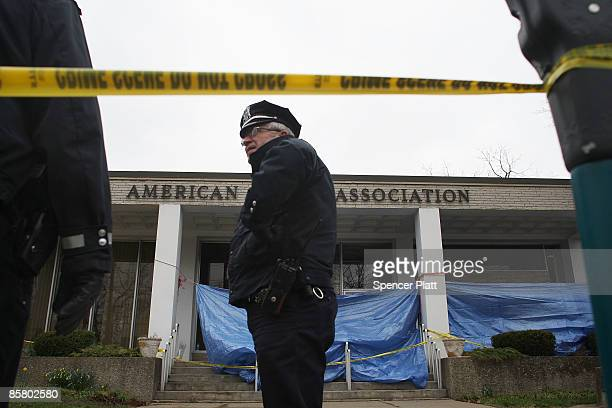Police officer stands in front of the American Civic Association where a gunman killed 13 people yesterday April 4, 2009 in Binghamton, New York. The...