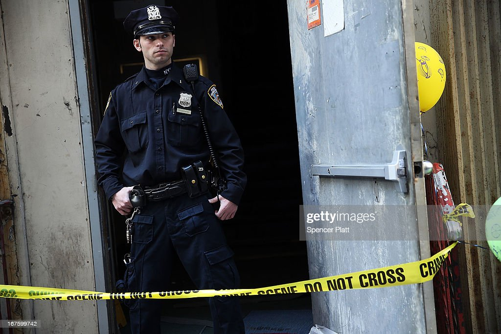 A police officer stands in front of the building on Park Place in lower Manhattan where a piece of landing gear believed to be from one of the planes destroyed in the September 11 attacks has been discovered on April 26, 2013 in New York City. The landing gear was discovered wedged between a mosque site and luxury high-rise apartment building, about three blocks north from the World Trade Center site.